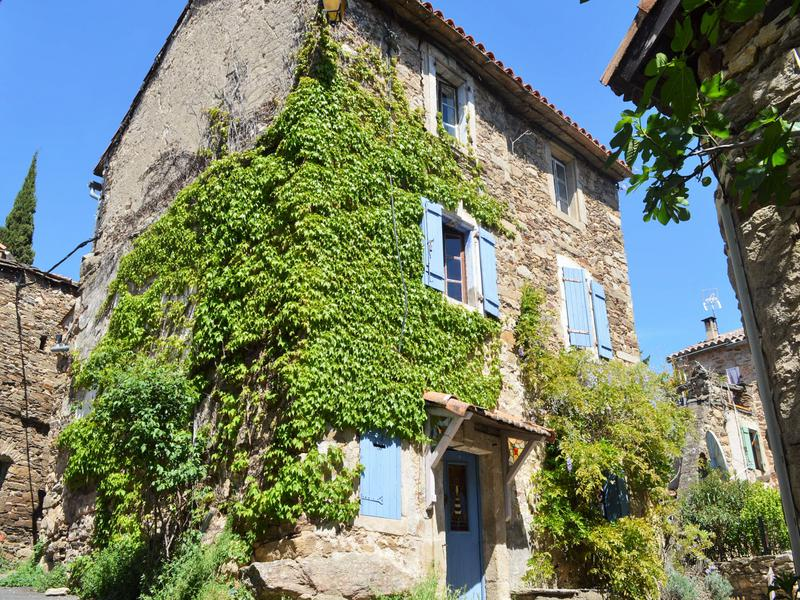 Rare opportunity to buy a beautiful character property in a cosmopolitan hamlet, above the river Orb, close to Olargues. This lovely property currently provides 2 bedrooms, a vaulted ground floor, a lovely entrance area and a room currently used as a bedroom/living room but that would make a perfect bedroom with ensuite (plumbing ready). On the first floor, there is a good-sized kitchen with a lounge area next to it as well as the bathroom. From the kitchen, you have access to the terrace of 20 m². On the upper level there is one big bedroom – that could easily be divided into two good sized bedrooms. The room before is a great landing area with a mezzanine to provide additional space. Lots of authentic feature such as stone flooring makes this a very unique property. It could benefit from updating to todays taste. The windows are all single glazing and tired – so new double-glazed windows are needed. The big bonus is the terrace of around 30 m² and the atelier space that is to be found underneath. Due to the location in the village there is no private parking with this property but there is parking close to the property on a first come first serve base. This is the perfect holiday home with great letting potential and is also suitable for all year round living if you install a heating device (edit: it appears there is a spot for a woodburner in the living area!).